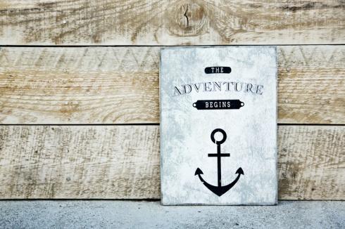 motivational  vintage poster on the rustic wood ADVENTURE BEGINS