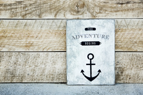 motivational  vintage poster on the rustic wood ADVENTURE BEGINS